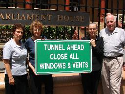 "Greens / RAPS Inc. holding sign ""Tunnel Ahead Close All Windows & Vents""..."